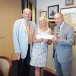 Izabela Rybak z Fundacji odbiera z rak przedstawicieli firmy Rojohns Financial Group czek dla dzieci